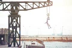 Brave man hanging on the crane Royalty Free Stock Photos
