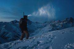 Brave man with headlamp, backpack and a snowboard behind his back climb night on snowy mountain. Man commit ski tour in high ridge. Backcountry. Great view on Royalty Free Stock Photos