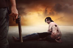 Brave man with jeans pants holding gun looking at zombie Royalty Free Stock Image