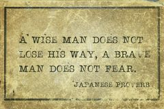 Brave man JP. A wise man does not lose his way, a brave man does not fear - ancient Japanese proverb printed on grunge vintage cardboard royalty free stock images