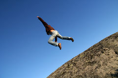 Brave man jumping from a cliff. Man jumping from a cliff over a blue clean sky Royalty Free Stock Image