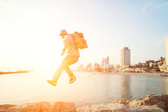Brave man jumping over rocks near sea. And city on the background Stock Photos