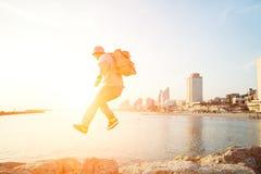 Brave man jumping over rocks near sea Stock Photos