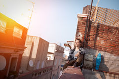 Brave man sitting on the edge on high roof looking far away, with backpack and skateboard. Young and brave man sitting on the edge on high roof looking far away Royalty Free Stock Images