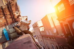Brave man sitting on the edge on high roof looking at map, with backpack and skateboard. Young and brave man sitting on the edge on high roof looking at map Stock Photos