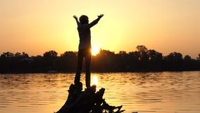 Brave man stands on tree roots on a lake bank in slo-mo. An inspiring view of a young man who stands on roots of a huge tree on a lake bank at sunset with a stock video