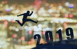 2019 brave man successful concept,silhouette man jumping over gap between building, city scape, landscape to 2019 new year, feel l royalty free stock photo