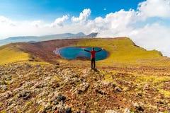 Man on a summit of Azhdahak volcano watching crater lake, Geghama mountains, Armenia royalty free stock photo