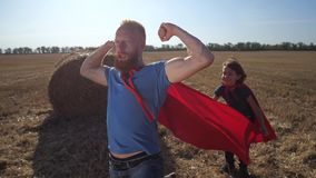 Brave man in superhero cape playing with son. Playful father and son in superhero costumes playing in nature at sundown. Bearded stern male looking into distance stock footage
