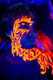 Brave man uv portrait neon face art, bright fire energy. Creative colorful makeup neon, glowing painting on face, ultraviolet picture, shiny orange fire on blue Stock Photos