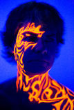 Brave man uv portrait neon face art, bright fire energy. Creative colorful makeup neon, glowing painting on face, ultraviolet picture, shiny orange fire on blue Stock Images