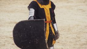 Brave man wearing steel armor standing on battle field with sword and shield. Stock footage stock footage