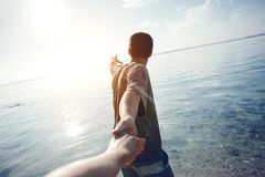 Brave man guiding traveling woman through the water in ocean royalty free stock photography