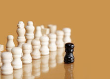 Brave Pawn. Opposition concept. Row of white chessmen against one black pawn Royalty Free Stock Image