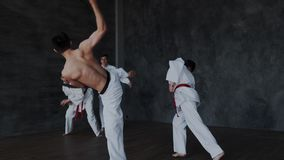 Brave powerful asian guy fighting alone against three strong warriors in white kimono. He perform active martial tricks