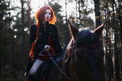 Brave red-haired girl in a black coat and a red dress with long hair gathered in a braid. A woman riding a horse in autumn forest, beautiful strong stallion Royalty Free Stock Photos