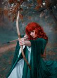 Brave red-haired girl holds a bow in her hands, directing an arrow, experienced hunter goes into battle, warlike image. Of the princess in emerald cloak and royalty free stock photos