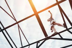 Brave and risky man balancing on the top of high metal bridge. Outdoors stock photo