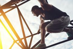Brave and risky man sitting on the top of high metal bridge. Outdoors Royalty Free Stock Photo