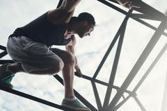 Brave and risky man sitting on the top of high metal construction. Outdoors Royalty Free Stock Image