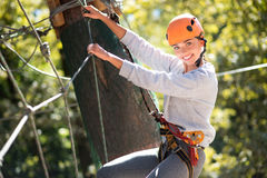 Brave skillful woman clambering in the high wire park. Being outdoors. Confident skillful elated woman holding on to the ropes and using special outfit while Stock Image