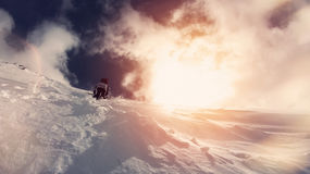 Brave snowboarder with a backpack climbs up the mountain. Lens flare effect, vintage color. Pyrenees, Andorra la Vella Royalty Free Stock Images