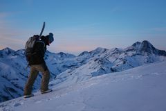 Brave snowboarder with backpack and snowboard climb at snowy mountain at evening. Wearing ski wear royalty free stock images