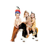 Brave and Squaws. Three children dressup as indians for Halloween.  Boy wears war bonnet and war paint while two girls wear deerskin dresses and moccasins and Stock Images