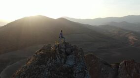 Brave stranger at the top of the rock watching the beautiful sunset over the valley Inspirational decision fill the