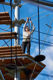 Brave teenager girl is climbing to amusement park Royalty Free Stock Photo