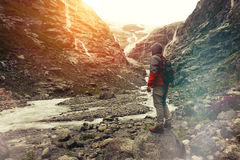 Brave traveler with a backpack looking at a glacier and is preparing for the ascent. Lens flare effect Royalty Free Stock Images