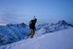 Brave traveler with backpack and a snowboard behind his back climbs winter mountain. Great view on snowy ridge Royalty Free Stock Photography