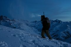 Brave traveler lights the way with a headlamp at night winter mountain. Snowboarder with backpack and a snowboard behind his back Royalty Free Stock Photos