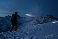 Brave traveler man commit ski tour on high mountain at night. Professional snowboarder lights the way with a headlamp. Backcountry. In great winter snowy Stock Images