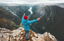 Brave traveler man raised hands traveling in Norway. Standing on cliff mountain active lifestyle weekend getaway adventure vacations success concept aerial stock images