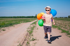 Brave traveller. Brave little boy traveller walking the country road with bunch of colorful balloons in the sunny weather Royalty Free Stock Image