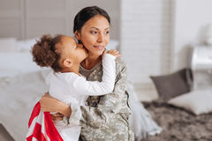 Brave woman delighted spending time with her family. Can finally relax. Graceful confident young mother hugging her little child after working away from home stock image