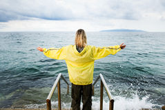 Brave woman greeting stormy. Ocean Royalty Free Stock Photos