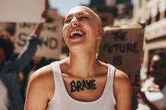 Brave woman with group of protesters in background. Bald woman laughing outdoors during a protest. Brave woman with group of protesters in background stock photos