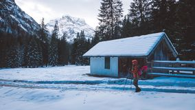 Brave woman hiker passing winter mountain valley. Woman hiker passing winter mountain valley near small chalet covered with snow Royalty Free Stock Photo
