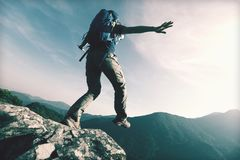 Brave woman hiker walking to the cliff edge. On mountain top royalty free stock images