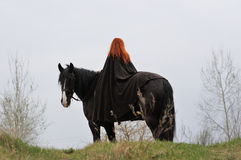 Brave woman with red hair in black cloak on friesian horse. Brave woman with red hair in black cloak on a purebred friesian horse, girl from the back royalty free stock photos