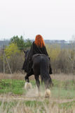 Brave woman with red hair in black cloak on friesian horse stock image