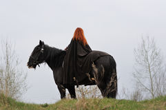 Brave woman with red hair in black cloak on friesian horse royalty free stock photo