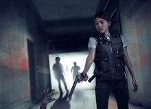Brave woman with vest shoot the zombies. Brave women with shoot the zombies on inside building Stock Photo