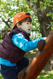 Brave young boy climb up on ladder Stock Image