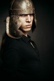 Brave young man. In roman helmet posing over dark background Royalty Free Stock Photo