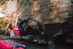 Brave young rock climber woman. Young rock climber woman on a cliff rock at the coast with safety mats Stock Image