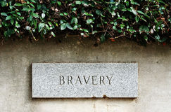 Bravery. Sign engraved in wall with shrub on top Royalty Free Stock Images