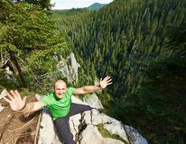 Bravery. Happy man sitting on the edge of a very high cliff Stock Photo